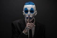 可怕的小丑和万圣夜题材:在黑暗的背景隔绝的黑衣服的疯狂的蓝色小丑在演播室 库存照片