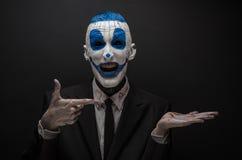 可怕的小丑和万圣夜题材:在黑暗的背景隔绝的黑衣服的疯狂的蓝色小丑在演播室 免版税库存照片