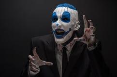可怕的小丑和万圣夜题材:在黑暗的背景隔绝的黑衣服的疯狂的蓝色小丑在演播室 免版税库存图片