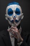 可怕的小丑和万圣夜题材:在黑暗的背景隔绝的黑衣服的疯狂的蓝色小丑在演播室 图库摄影
