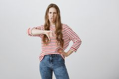 可怕的想法,女孩陈列反感 皱眉,伸出舌头和显示拇指的生气的感情少妇 免版税图库摄影