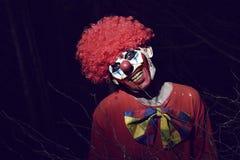 可怕邪恶的小丑在森林在晚上 免版税库存照片