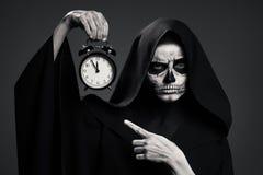可怕死亡举行一块手表在他的手上 免版税库存照片