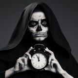 可怕死亡举行一块手表在他的手上 免版税图库摄影