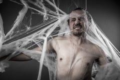 可怕network.man在巨大的白色蜘蛛网缠结了 图库摄影
