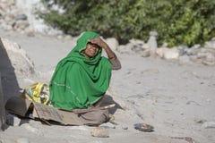 可怜的妇女为从一个路人的金钱乞求在街道上在Leh,拉达克 印度 图库摄影