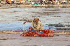 可怜的妇女休息与一个瓶水在空的Meena Bazaa 免版税库存照片