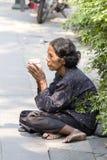 可怜的妇女叫化子坐边路在曼谷,泰国 图库摄影