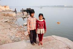 可怜的孩子在河甘加的河岸走 免版税库存图片