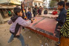 从可怜的家庭的未认出的少年充当乒乓球在贫民窟, 2013年12月20日在加德满都,尼泊尔 库存图片