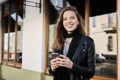 可您帮助我发现这个咖啡馆 时髦衣裳的走与朋友的可爱的女学生室外射击  库存照片