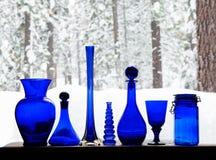 可收回的蓝色玻璃瓶在反对雪森林的窗口里 免版税库存照片