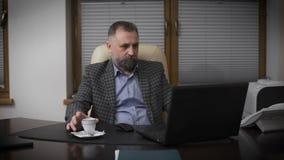 可敬的绅士变老与graying头发 院长在他的办公室与膝上型计算机和饮用的咖啡一起使用 股票录像