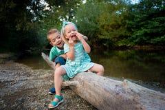 可爱兄弟姐妹使用傻由河,夏天户外概念 免版税库存图片