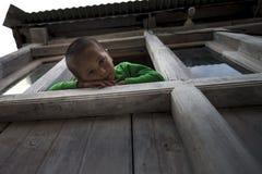 可爱和嬉戏的年轻男孩攀登和坐在家窗口非常突出的壁架,看下来和腿  免版税库存图片