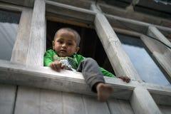 可爱和嬉戏的年轻男孩攀登和坐在家窗口非常突出的壁架,看下来和腿  免版税库存照片