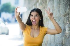 可爱和甜拉丁与手机的妇女微笑的愉快的采取的自画象selfie照片 图库摄影
