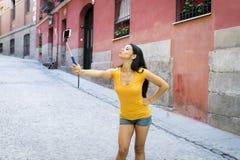 可爱和甜拉丁与手机的妇女微笑的愉快的采取的自画象selfie照片 免版税图库摄影