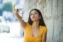 可爱和甜拉丁与手机的妇女微笑的愉快的采取的自画象selfie照片 免版税库存照片