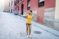 可爱和甜拉丁与手机的妇女微笑的愉快的采取的自画象selfie照片 库存图片