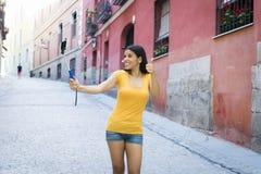 可爱和甜拉丁与手机的妇女微笑的愉快的采取的自画象selfie照片 免版税库存图片