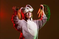 可爱和逗人喜爱的兔子女孩用红萝卜 免版税库存照片