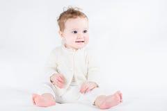 可爱女婴佩带的白色毛线衣开会和使用 免版税图库摄影
