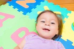 可爱女婴说谎的微笑 免版税库存照片
