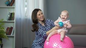 可爱婴儿跳跃在球和笑,获得的婴孩与爱恋的母亲的乐趣 影视素材