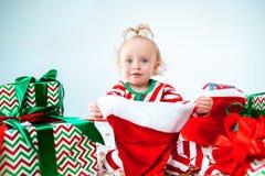 可爱宝贝女孩戴圣诞老人帽子的1岁摆在圣诞节背景 坐与圣诞节球的地板 免版税库存照片
