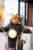 可爱宝贝男孩坐摩托车 免版税库存照片