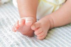 可爱宝贝脚和软的皮肤在床上 免版税图库摄影