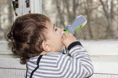 可爱宝贝饮用的汁液或酸奶从瓶 一个一岁的孩子的情感画象 库存照片