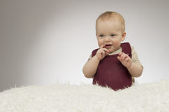 可爱小男孩微笑,坐白色毯子,演播室射击,隔绝在灰色背景,滑稽的婴孩画象 免版税库存图片