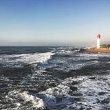 可爱灯塔的海滩 库存图片