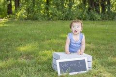 可爱的一个岁女孩坐条板箱 库存图片