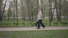 可爱的一起走在公园的祖父和逗人喜爱的矮小的孙子 世代概念 友好的家庭 股票录像