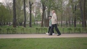 可爱的一起走在公园的祖父和逗人喜爱的矮小的孙子 世代概念 友好的家庭 股票视频