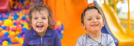 可爱的两个微笑的小女孩和男孩 画象 愉快的子项 免版税库存图片