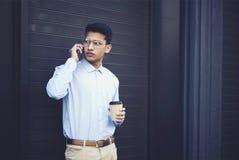 可爱的严肃的少年在有时髦的衣物穿戴了与朋友的交谈 免版税库存照片