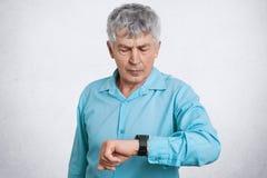 可爱的严肃的成熟商人看手表,在餐馆等待伙伴,穿戴在蓝色正式衬衣,立场a 免版税库存图片