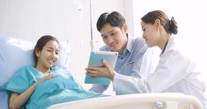 可爱的亚洲夫妇在医房激发家长看在数字片剂的语图图片 股票录像