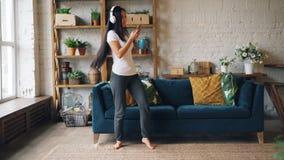 可爱的亚裔夫人在地板上听到在耳机的音乐,使用智能手机并且跳舞在客厅藏品 股票录像