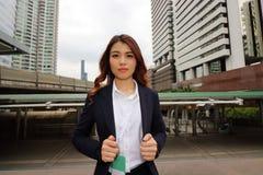 可爱的亚裔女商人画象城市背景的 免版税库存图片