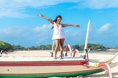 年轻可爱的亚裔妇女五颜六色的画象性感的白色礼服的在热带海滩巴厘岛,印度尼西亚 免版税库存照片
