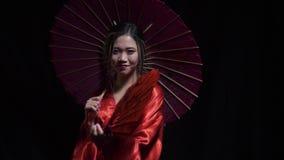 可爱的亚裔妇女展开一个红色爱好者,然后盖她的在慢动作的面孔 股票视频