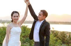 可爱的亚裔新娘和新郎跳舞反对日落场面 免版税图库摄影