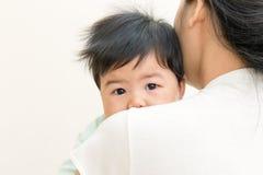可爱的亚裔婴孩病和不快乐在妈妈肩膀 免版税库存照片