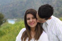 可爱的亲吻的人偎依的妇女 免版税库存照片