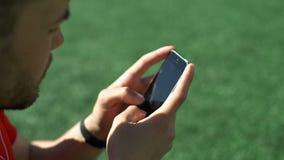 可爱的人听音乐和发短信在体育场草坪的智能手机 影视素材